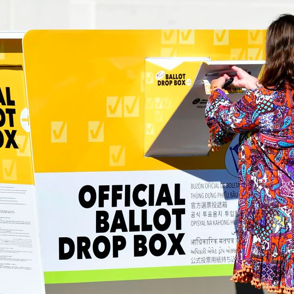 A woman casts her ballot for the 2020 US Elections at an official Orange County ballot drop-box